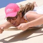 girl sandboarding in cap